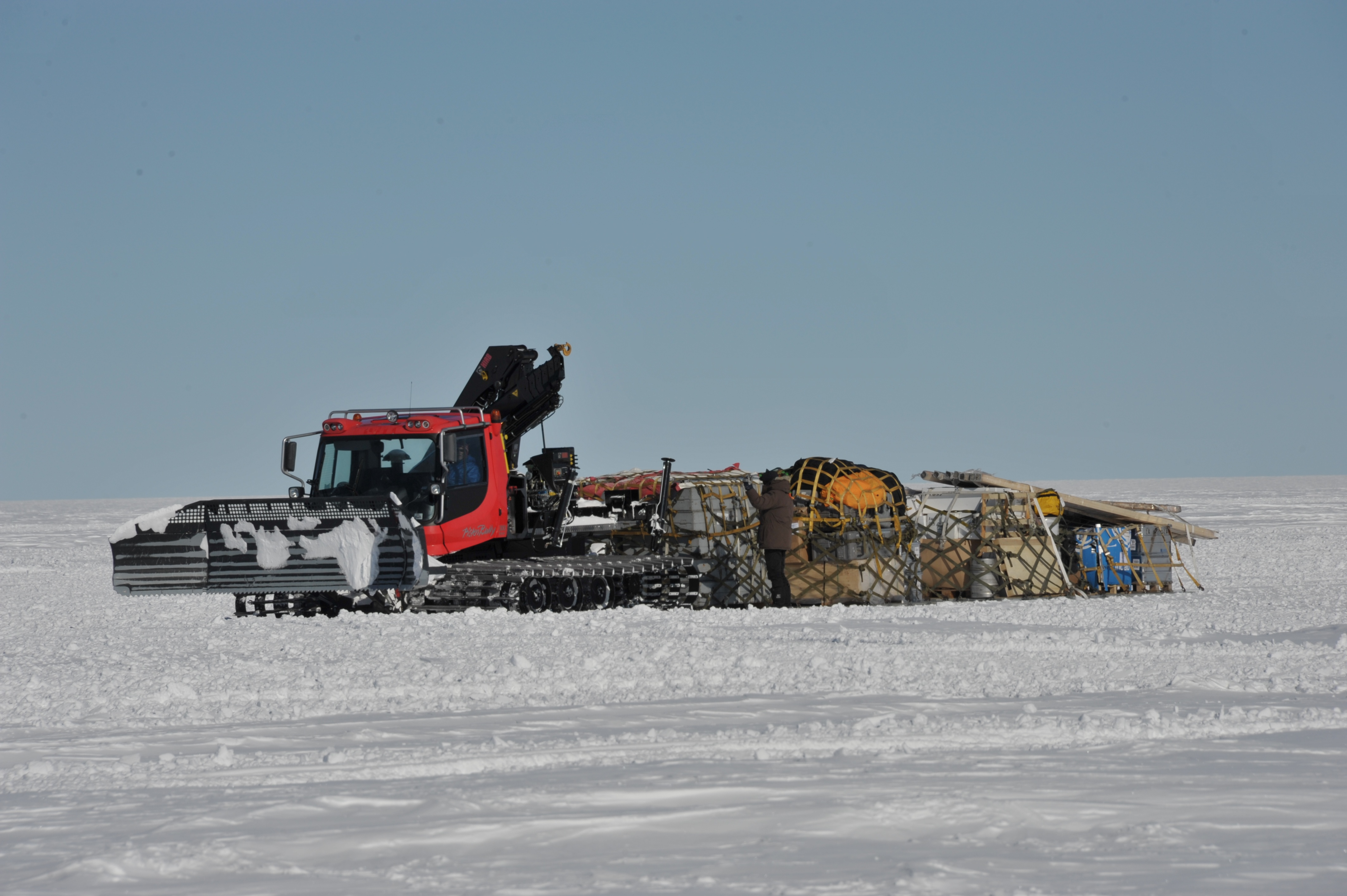 Pistenbully dragging 4 pallets of newly arrived cargo into camp