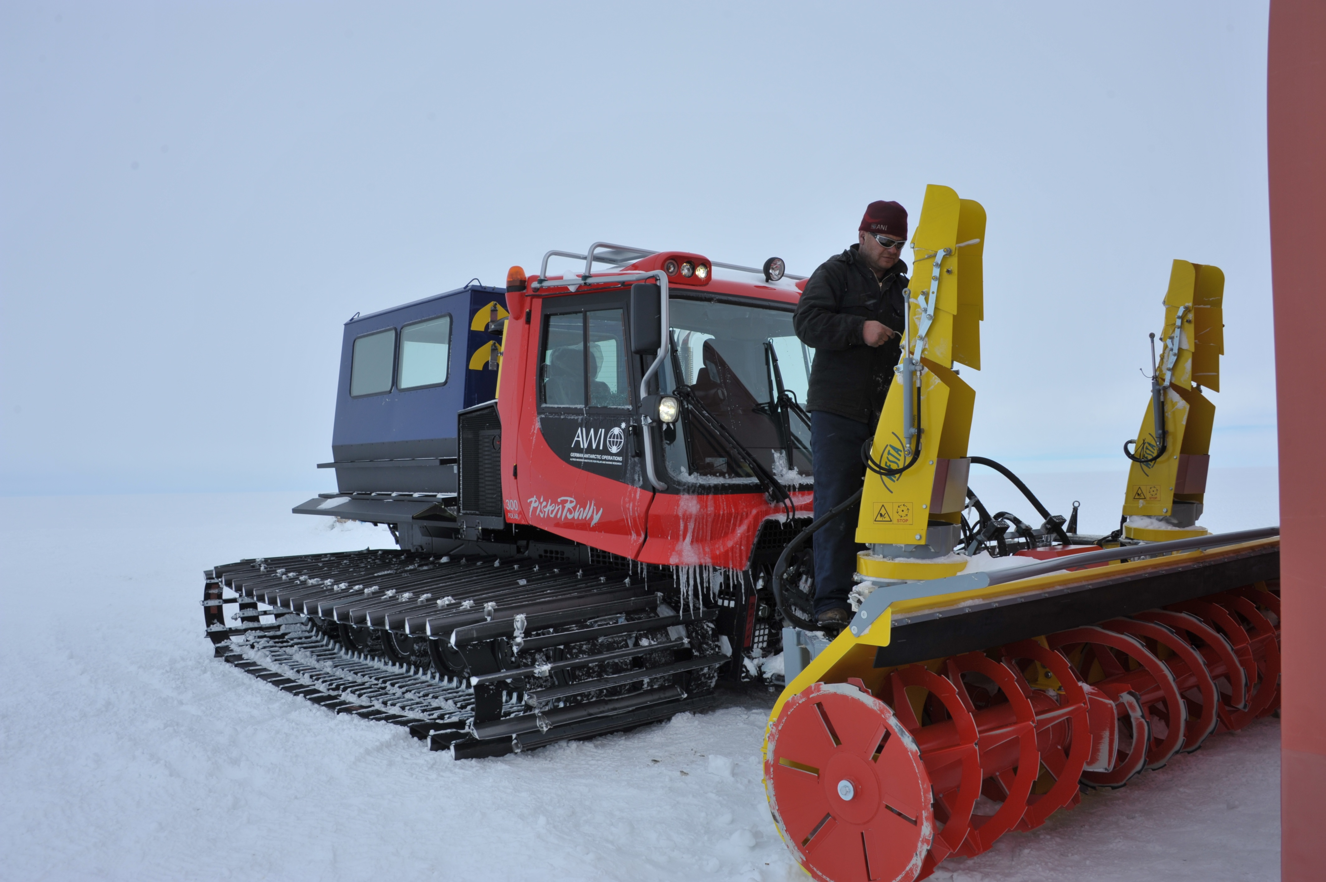 Chris mounting the snow blower on the pistenbully • EastGRIP