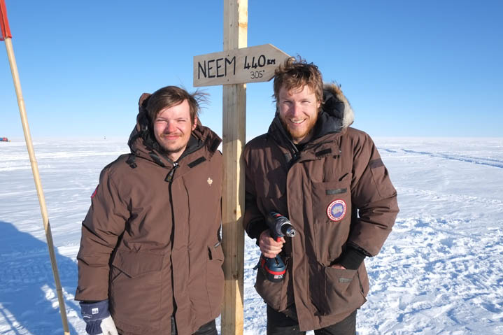 Mathias and Joel at the new road sign in the middle of EGRIP camp. It points to NEEM 440 km away.
