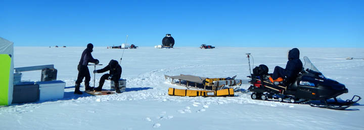 Helle and Paul are taking snow samples, while Anna is watching the traverse train go by. To the right the snowmobile with radar equipment is seen.